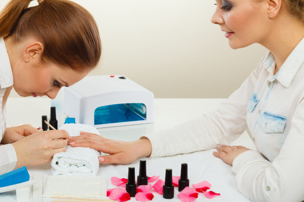 Manicure process concept. Young beautician and woman customer in beauty salon. Female client holds hands on deskop with nail polishes towel file lighting instruments.