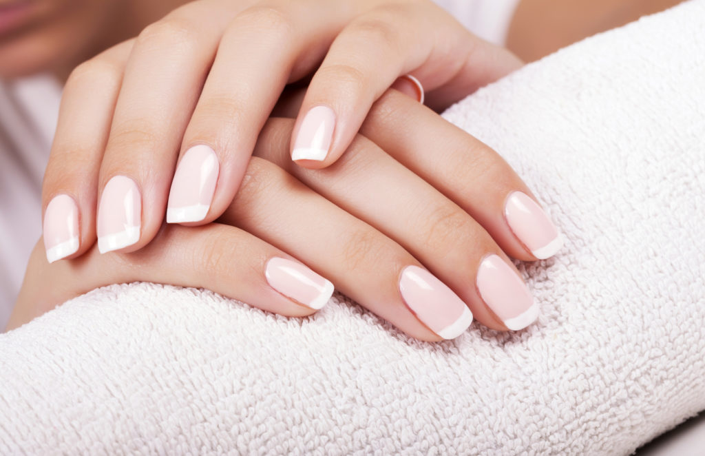 Beautiful woman's nails with french manicure.
