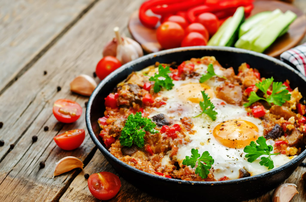 fried eggs with peppers, tomatoes, quinoa and mushrooms. the toning. selective focus
